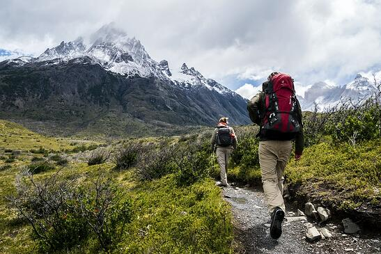 two person walking towards mountain covered with snow