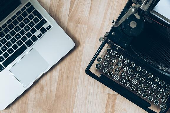 MacBook beside typewriter machine