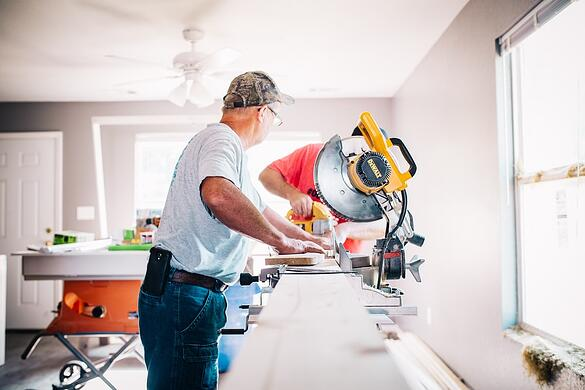 man standing infront of miter saw