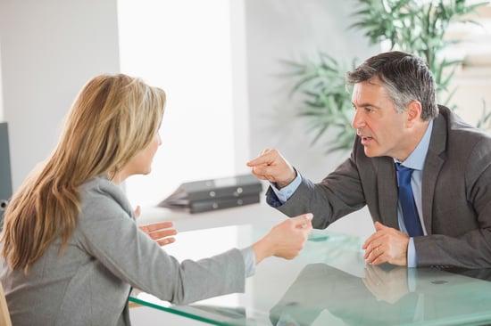 A blonde businesswoman and a mature businessman having an argument in an office