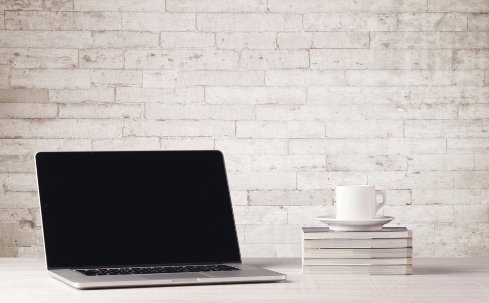 An open laptop on an office desk with flower, coffee, books in front of white brick wall background concept-1