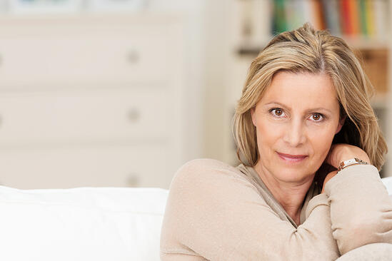 Attractive sincere middle-aged woman sitting on a sofa leaning her head on her raised arm looking directly at the camera with a serious expression-1