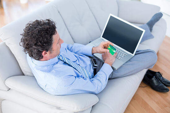 Businessman doing online shopping on couch in living room