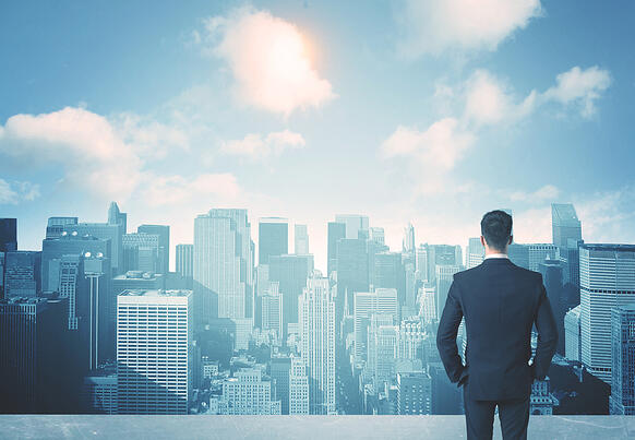 Businessman standing on a roof and looking at future city-1