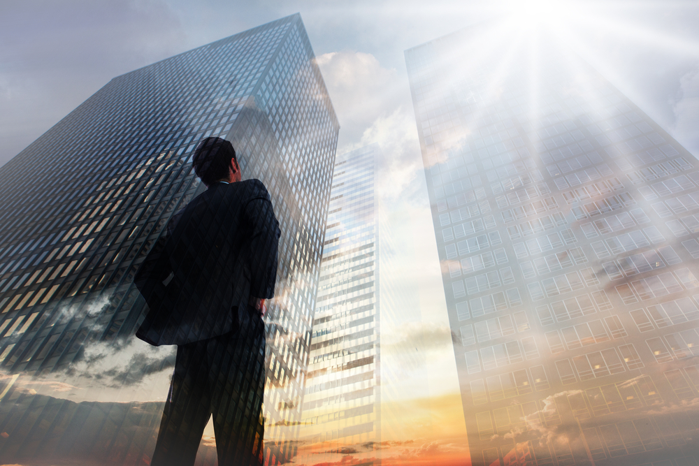 Businessman standing with hands on hips against low angle view of skyscrapers at sunset-2
