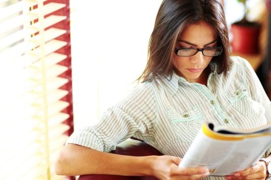 Businesswoman reading magazine in modern office