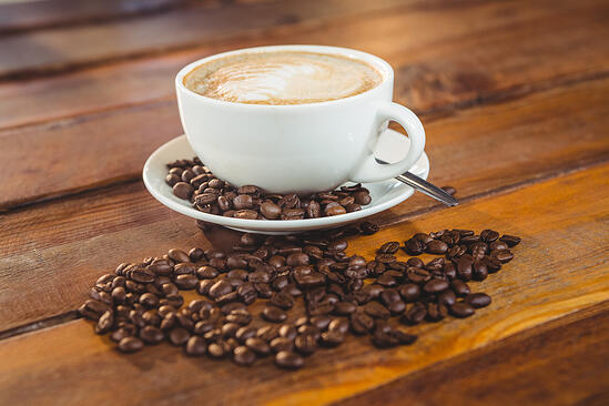 Cappuccino with coffee beans on table in cafeteria-1