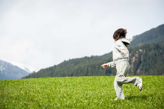Child on beautiful mountain field