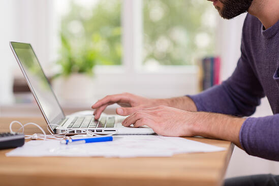 Close up low angle view of a man working from home on a laptop computer sitting at a desk surfing the internet-1