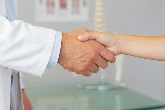 Close up of patient shaking hands with doctor in bright office