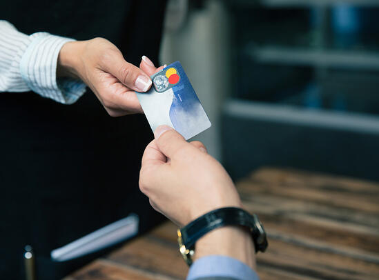 Closeup image of a man paying with credit card at the restaurant