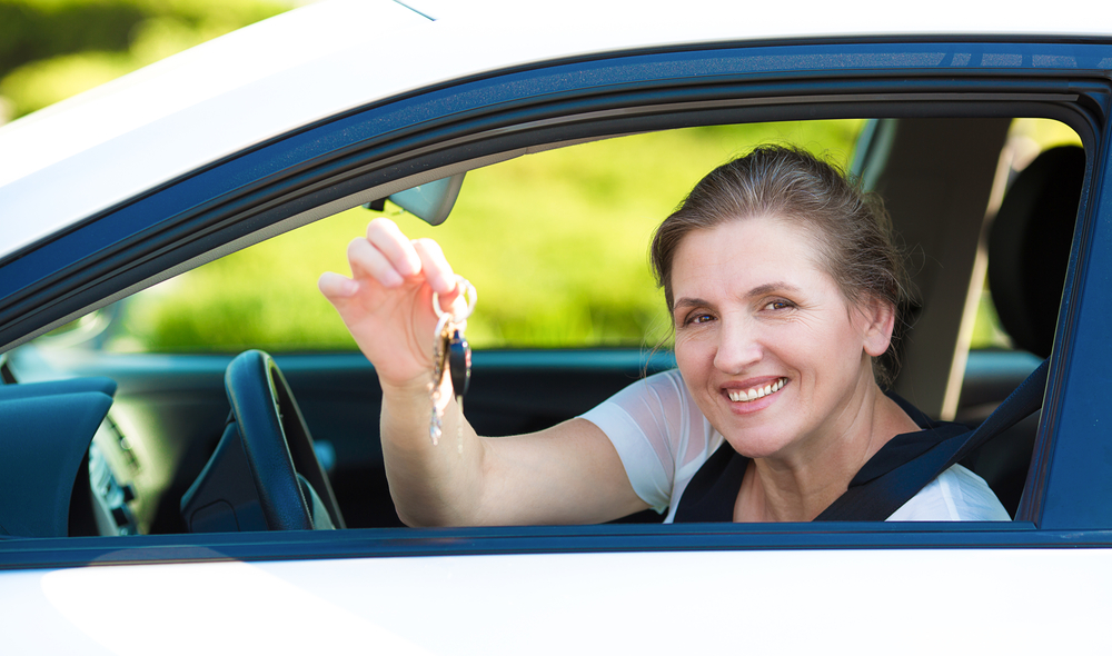 Closeup portrait happy, smiling, attractive woman, buyer sitting in her new white car showing keys isolated outdoors street dealership lot background. Personal transportation, auto purchase concept