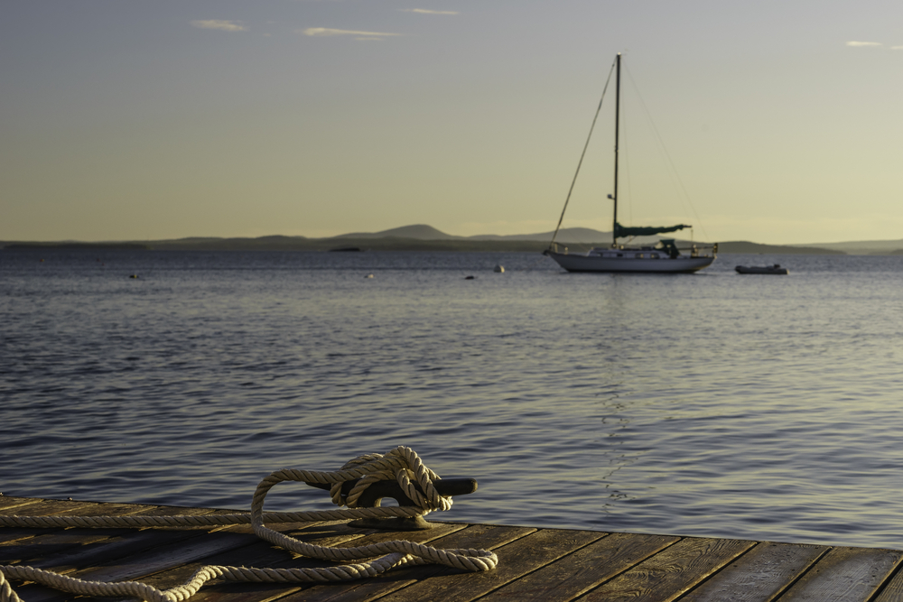 Coastal study in nautical preference Rope tied to cleat on dock in foreground to secure a boat off camera, while a sailboat lies at anchor beyond, at sunrise in New England (foreground focus)