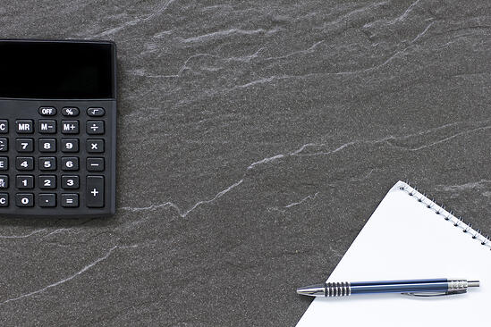 Concept displaying a calculator and note pad on a office desk