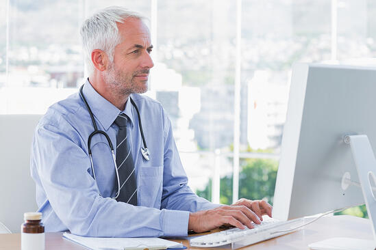 Doctor typing on his computer in the office-2