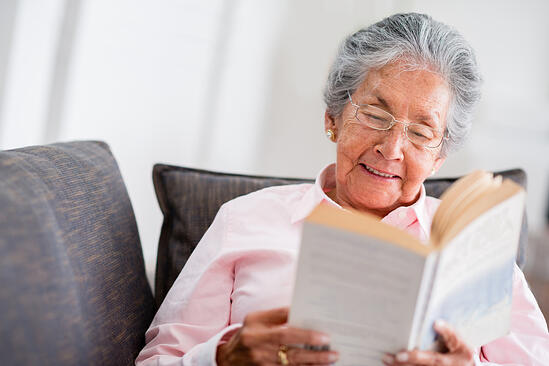 Elder woman reading a book at home and smiling-1