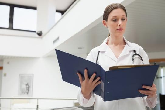 Female doctor reading  folder in hospital corridor