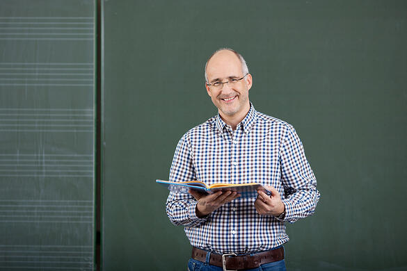 Friendly male teacher teaching form a set of class notes standing in front of a blank green blackboard with copyspace
