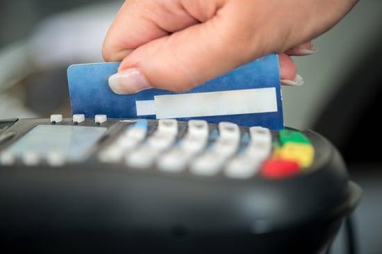 Hand swiping debit card on pos terminal