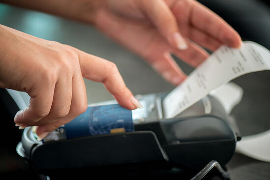Hand taking receipt from pos terminal
