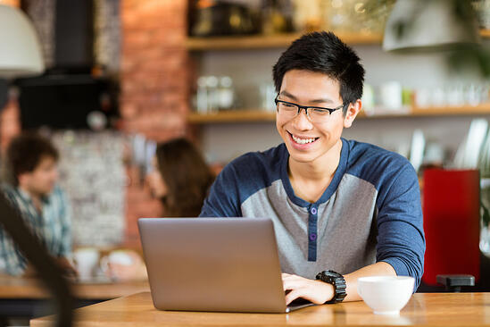 Happy cheerful young asian male in glasses smiling and using laptop in cafe-1