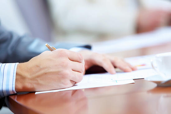 Image of businessmans hands signing documents at meeting