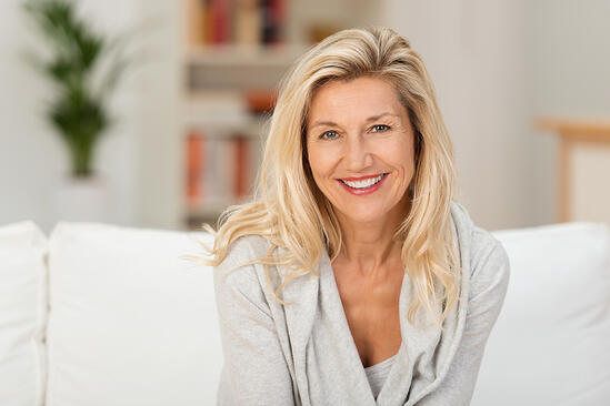 Lovely middle-aged blond woman with a beaming smile sitting on a sofa at home looking at the camera-2