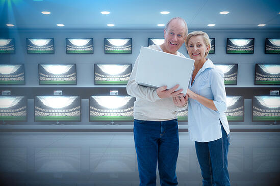 Mature couple smiling at camera with laptop against televisions for sale