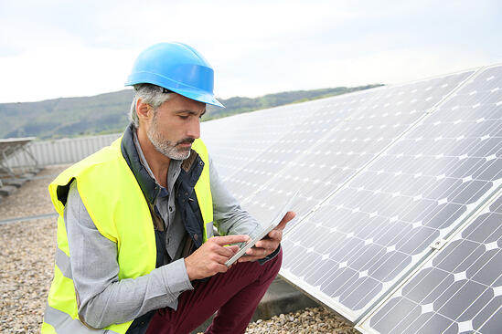 Mature engineer on building roof checking solar panels
