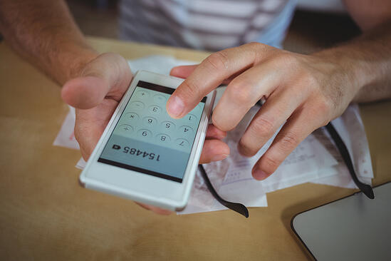 Mid section of man calculating bills on mobile phone-2