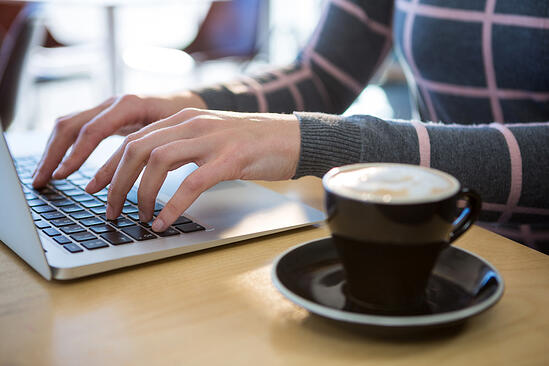 Mid section of woman using laptop with coffee on table in cafeteria