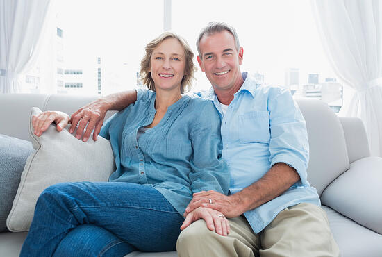 Middle aged couple relaxing on the couch smiling at camera at home in the living room-1