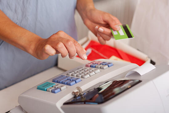 Midsection of saleswoman holding credit card while using ETR machine at boutique counter