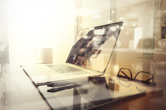 Office workplace with laptop and smart phone on wood table and london city blurred background-1