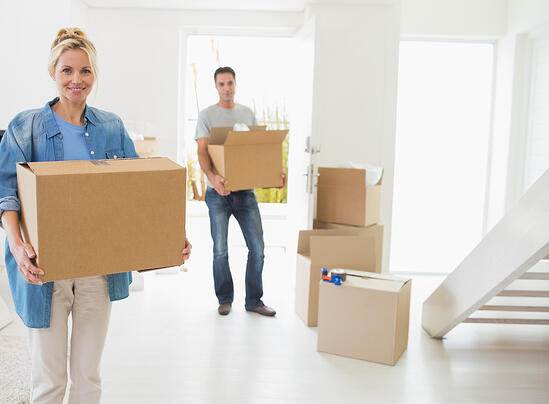Portrait of a smiling couple moving together in a new house