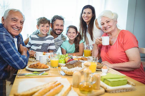 Portrait of happy multi-generation family sitting at breakfast table in home-1