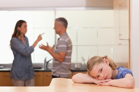 Sad little girl listening her parents having an argument in a kitchen