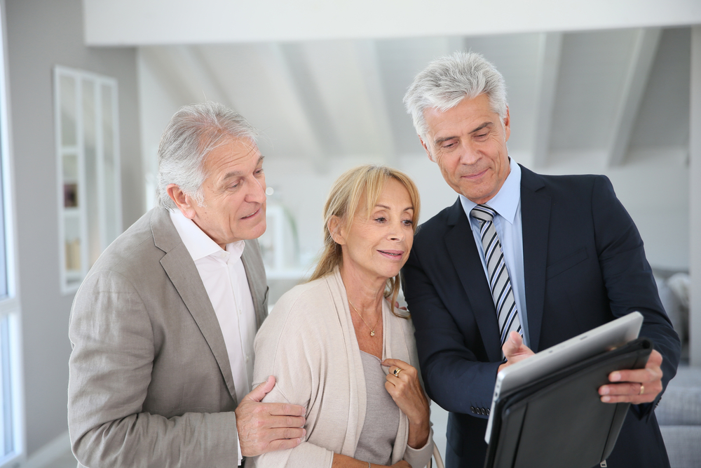 Senior couple with real-estate agent visiting house for sale-1