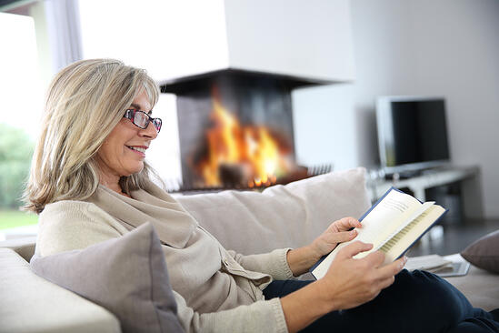 Senior woman reading book at home by fireplace-1