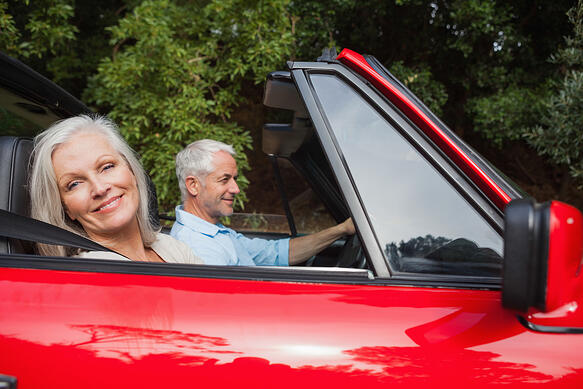 Side view of mature couple driving red convertible on bright day