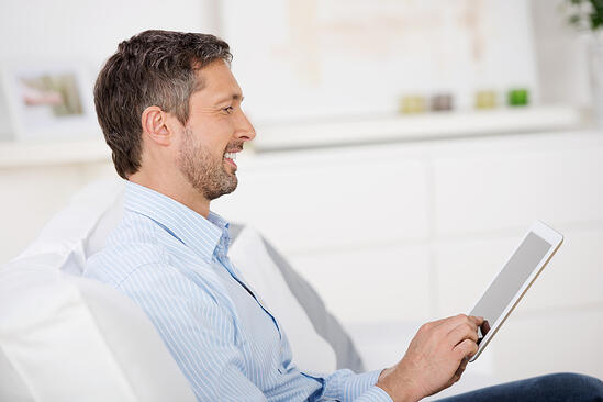 Side view of mature man reading ebook at tablet pc while sitting on sofa at home