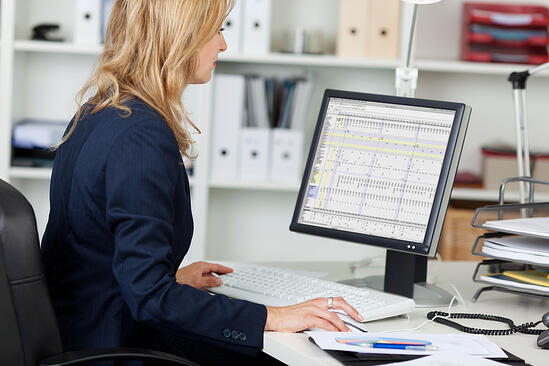 Side view portrait of businesswoman using computer at office desk-1