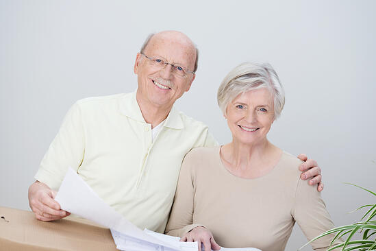 Smiling affectionate senior couple standing with the husbands arm around his wife looking at documents resting on a brown cardboard carton as they plan their move to a new home