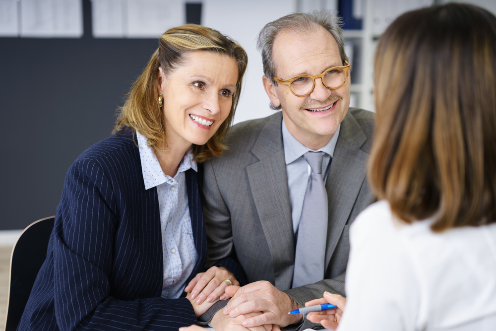 Smiling middle-aged couple in a meeting with an investment adviser planning for their future retirement, over the shoulder view-1