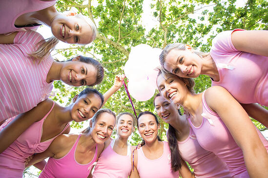 Smiling women in pink for breast cancer awareness on a sunny day-1