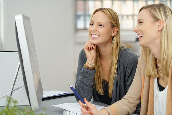 Two Happy Young Businesswoman Laughing While Working on the Computer at the Table Inside the Office.