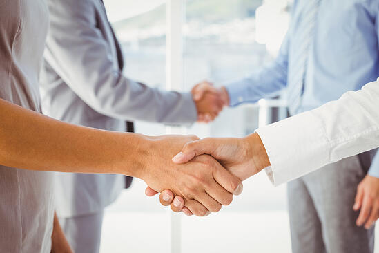 Two fellow employees shaking hands at work