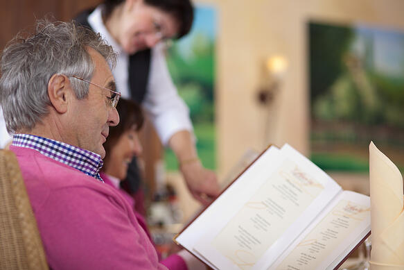 smiling guest in restaurant reading the menu with waitress in background-1