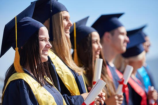 young graduates students group  standing in front of university building on graduation day